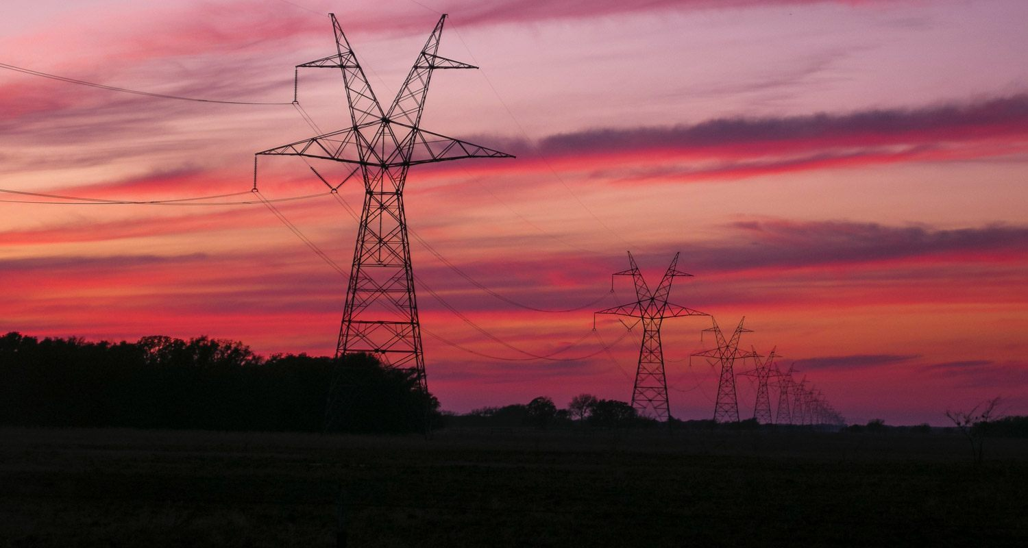 Overhead power lines extend into horizon at dusk