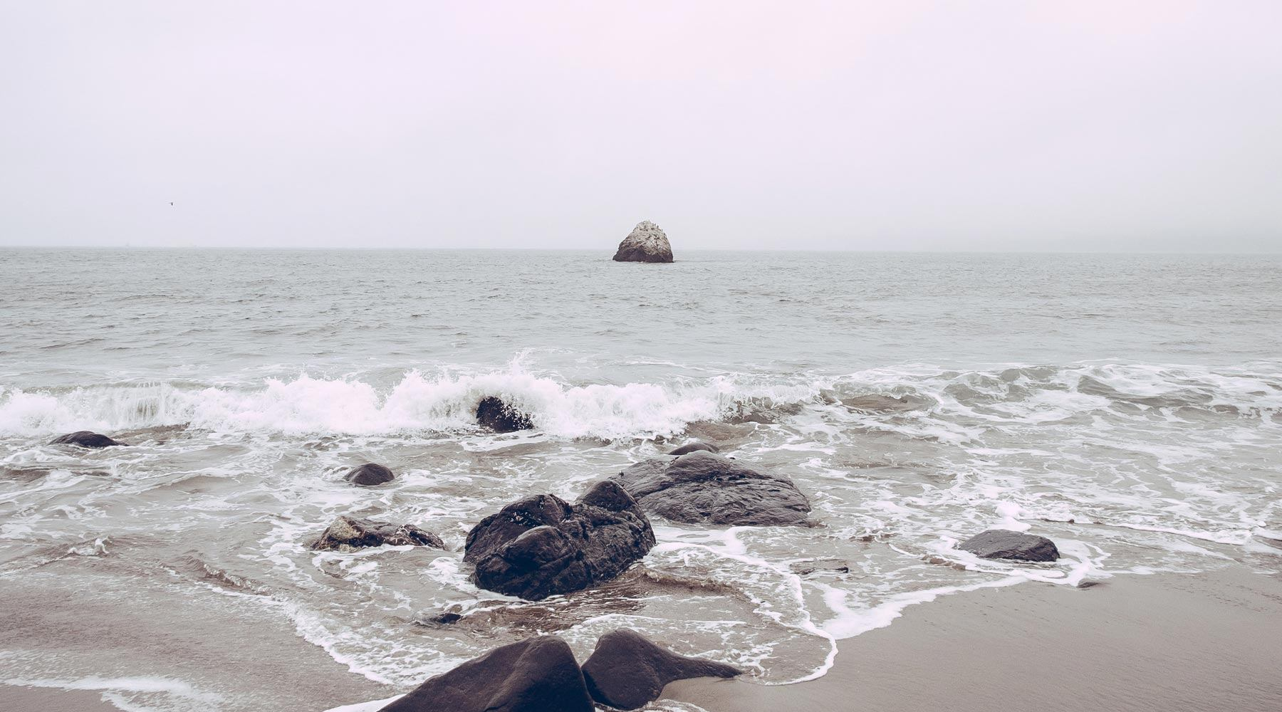 Waves hitting boulders and sand on shoreline on an overcast day