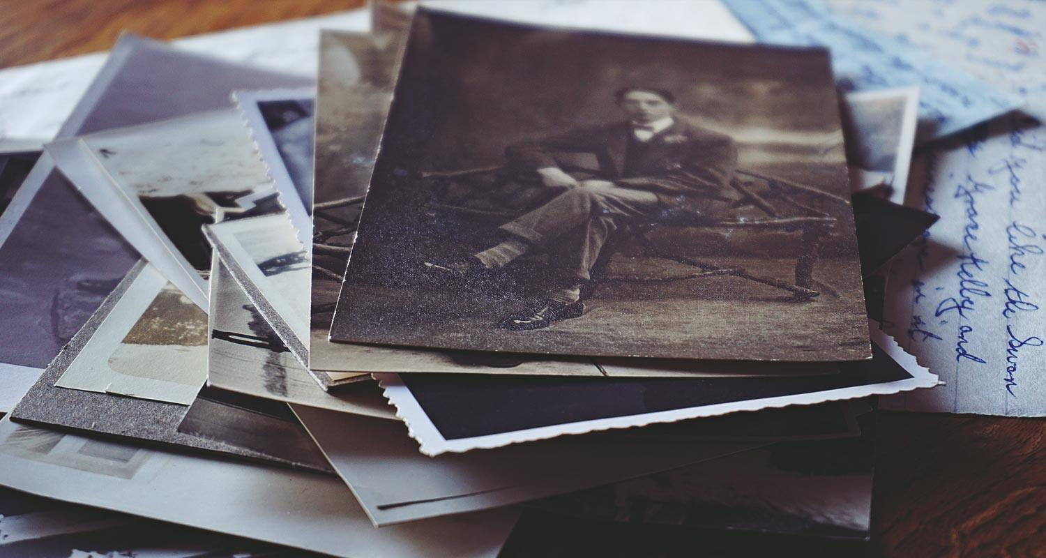 Stack of vintage photos beginning with image of young man sitting on bench